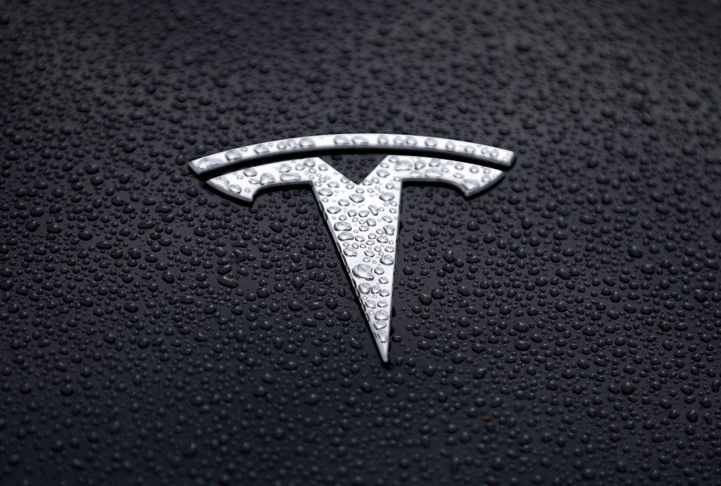 A silver Tesla logo on a black Tesla  in the rain in California