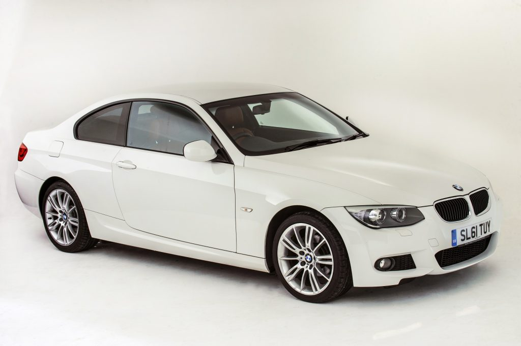 A white 2011 BMW 335i coupe is a hell of a luxury car, seen here in white shot from the front 3/4 view
