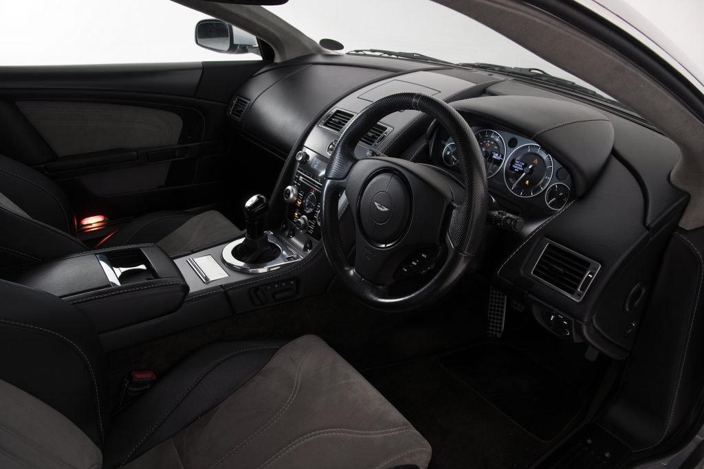 The interior of an Aston Martin DBS, complete with manual transmission