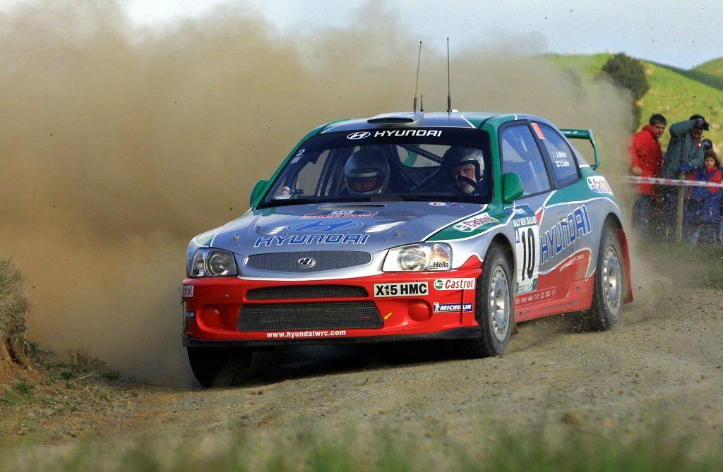 Dean MacRae in a Hyundai Accent rally car kicking up dirt mid-corner