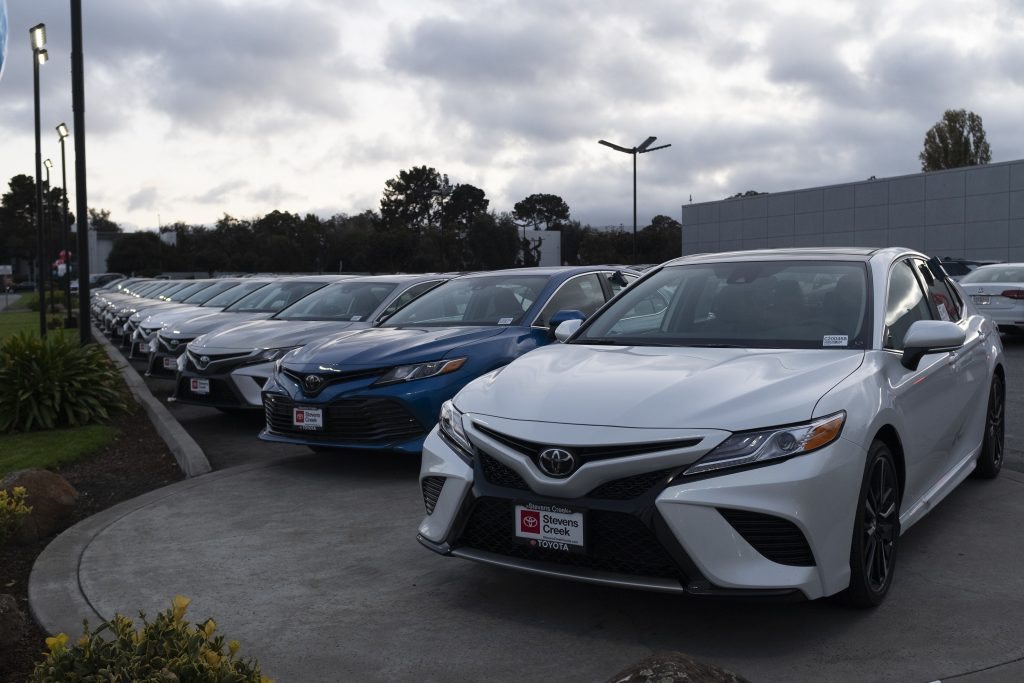 A row of Toyota Camry sedans at a dealership in California