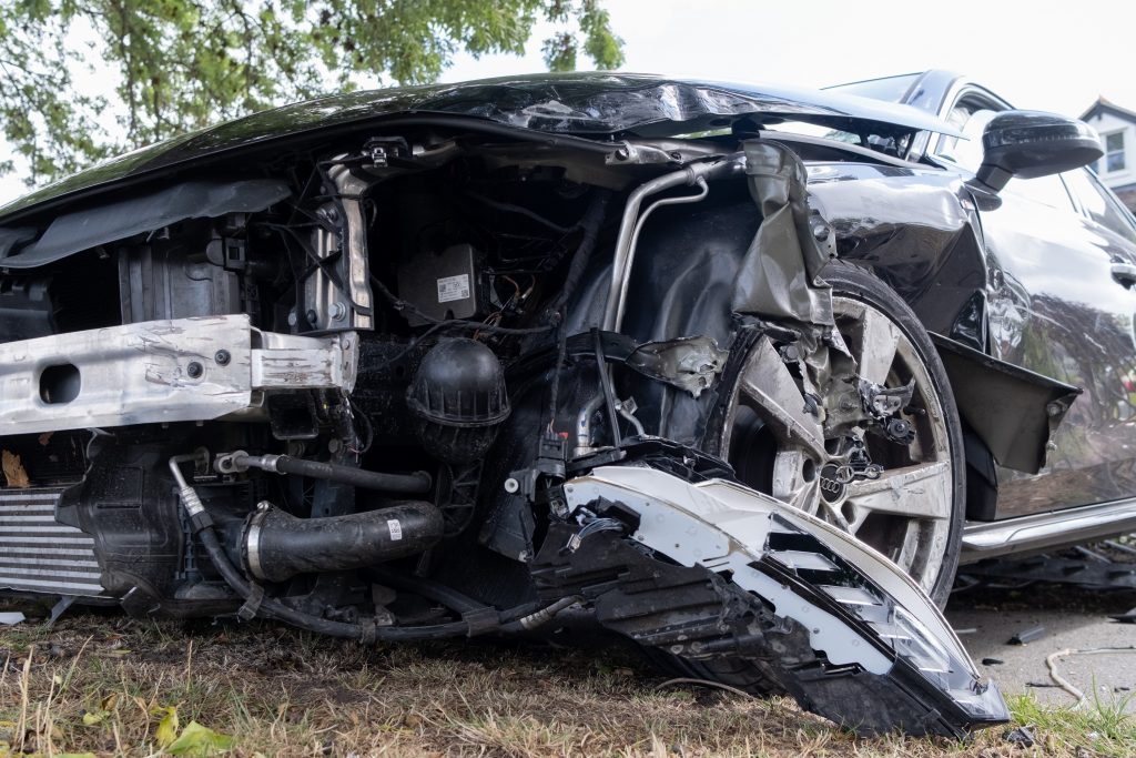 A wrecked Audi with the front bumper missing