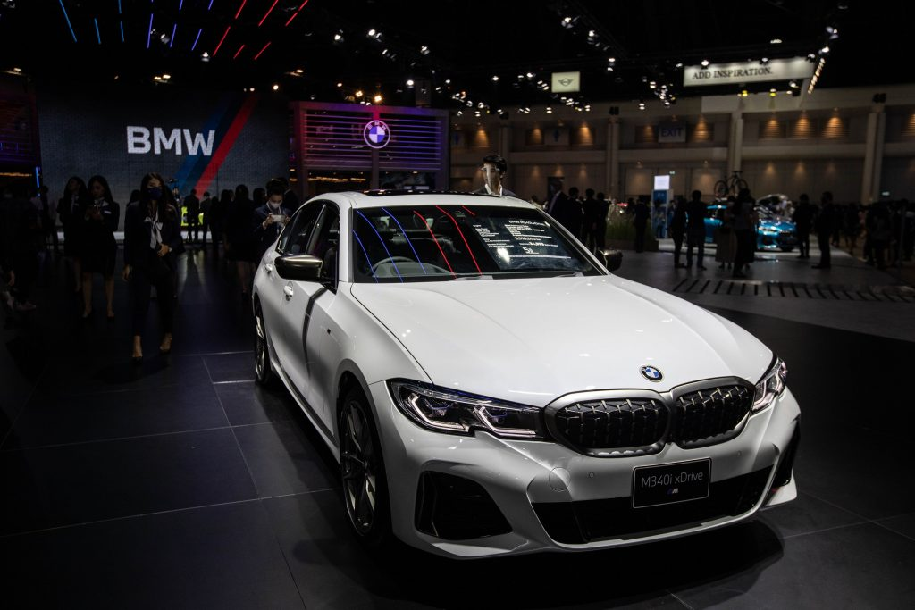An Alpine White 2021 BMW M340i under the showroom lights shot from the high front 3/4 angle