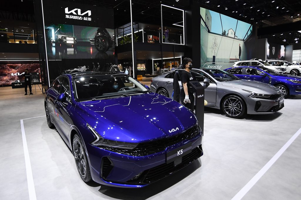 A blue 2022 Kia K5 under the lights at an auto show