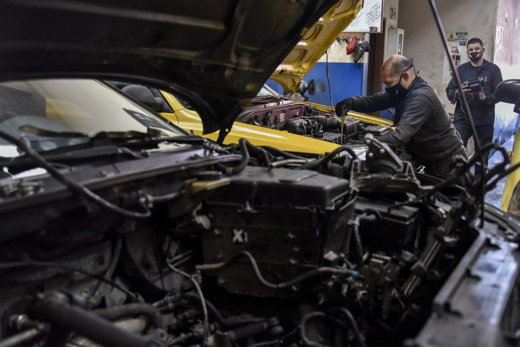 Mechanics conduct work on two cars with their hoods open. Work like this, done in a shop can be covered under an extended car warranty