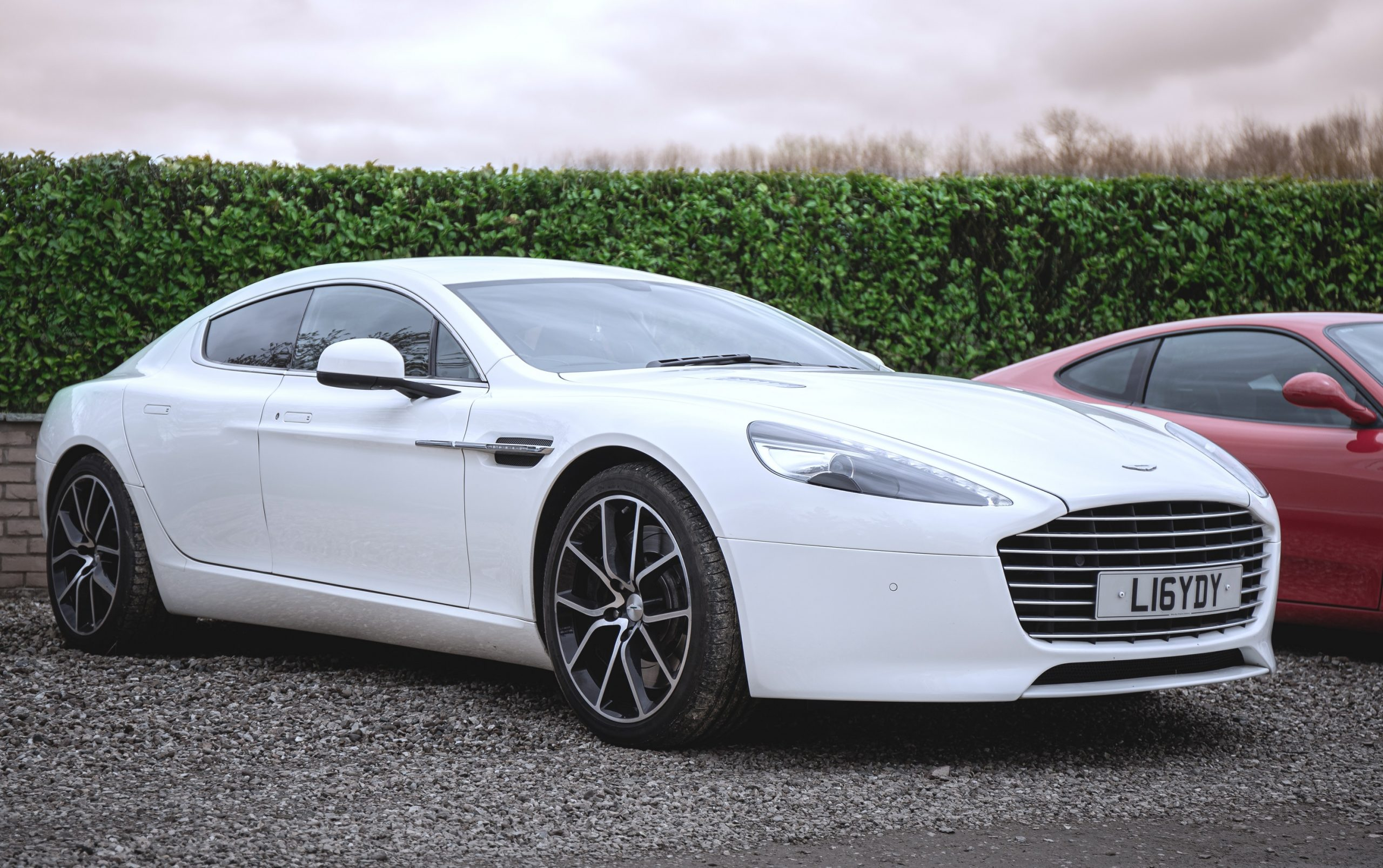 A white Aston Martin Rapide at an auto show in the UK, seen from the front 3/4 angle