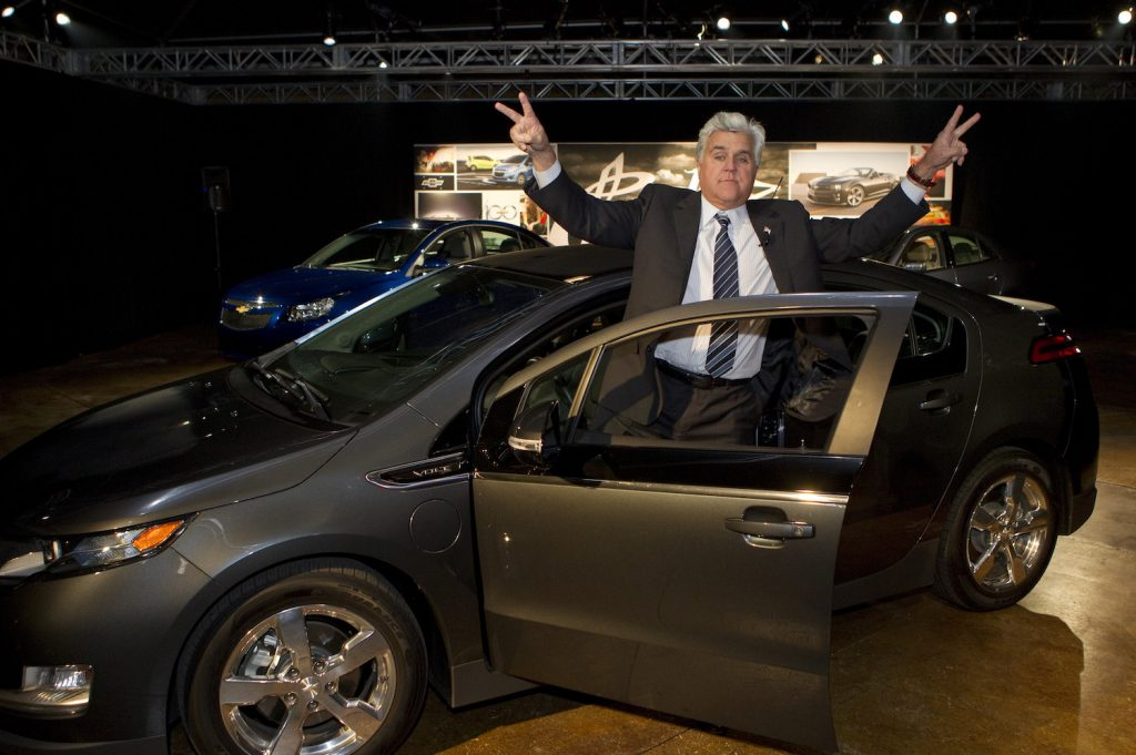 LOS ANGELES, CA - NOVEMBER 15:  In this handout photo provided by General Moters, Comedian, Tonight Show Host and auto enthusiast Jay Leno greets the audience after steering his personal Chevrolet Volt electric vehicle - with over 10,000 electric miles driven - into an event at the J Lounge November 15, 2011 in Los Angeles, California.  Leno said he has almost 10,500 miles driven and only 88 are not electric.  (Photo by Dan MacMedan/Chevrolet News Photo via Getty Images)