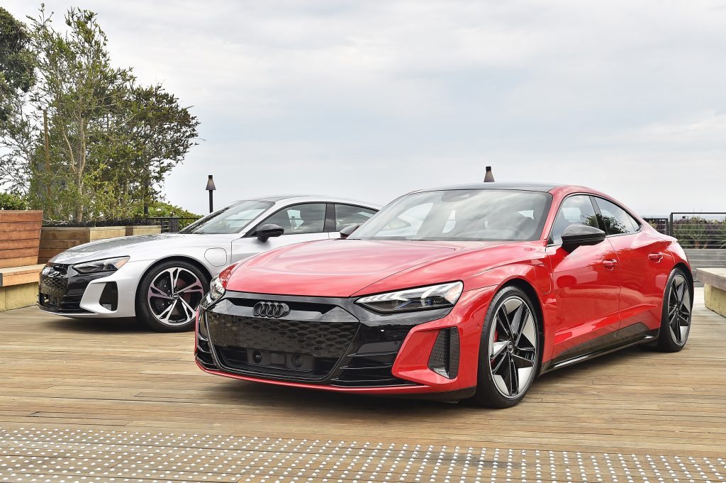 A red and silver Audi RS e-tron GT photographed as a pair from the front 3/4 angle