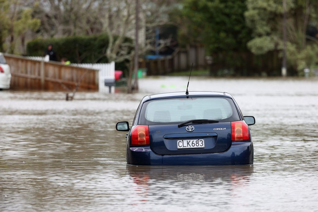 A blue Toyota Corolla wades through a flooded street in New Zealand