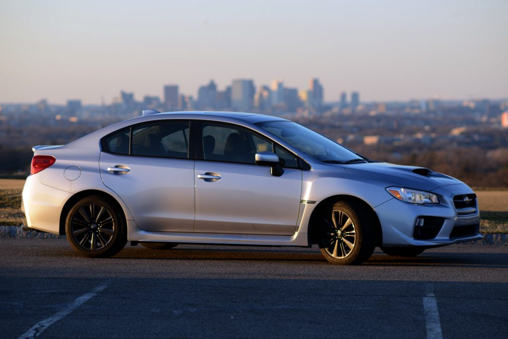 A silver 2015 Subaru WRX, shot in profile at sunset in a parking lot