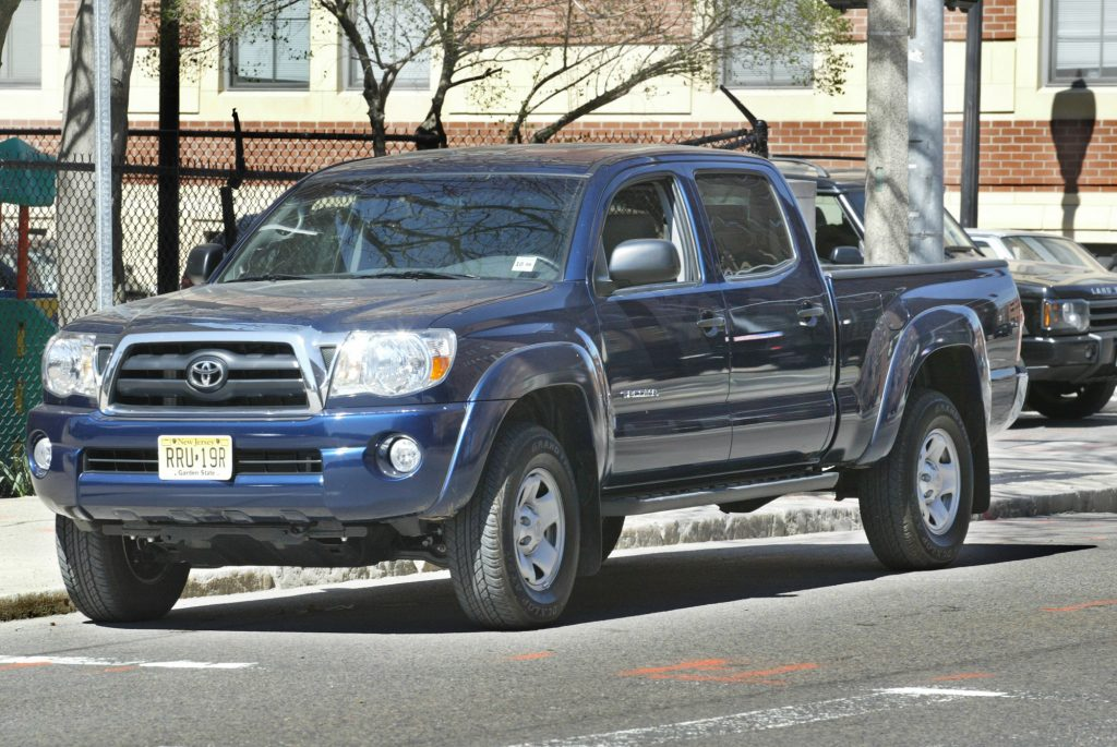 A blue Toyota Tacoma pickup truck is parked on a street.