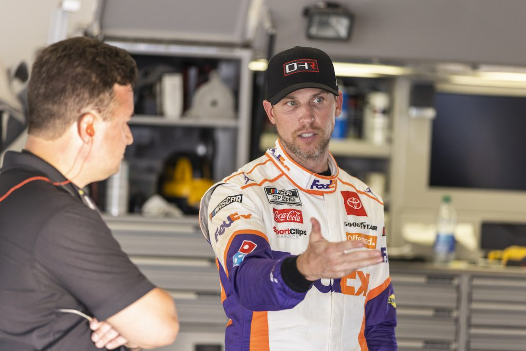 Denny Hamlin, Driver of the #11 NASCAR Next Gen car, talks with a team member in the Daytona garage during tests. The Next Gen rearview camera is highlighting a generational divide between Hamlin and younger drivers.   James Gilbert/Getty Images