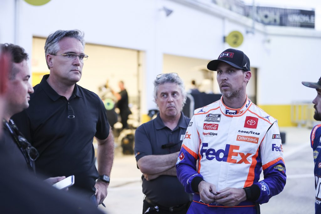 Denny Hamlin, team owner and Driver of the #11 NASCAR Next Gen car, talks with NASCAR personnel. Some drivers are complaining that NASCAR's Next Gen Cars Are Too Hot To Drive   Photo by James Gilbert/Getty Images