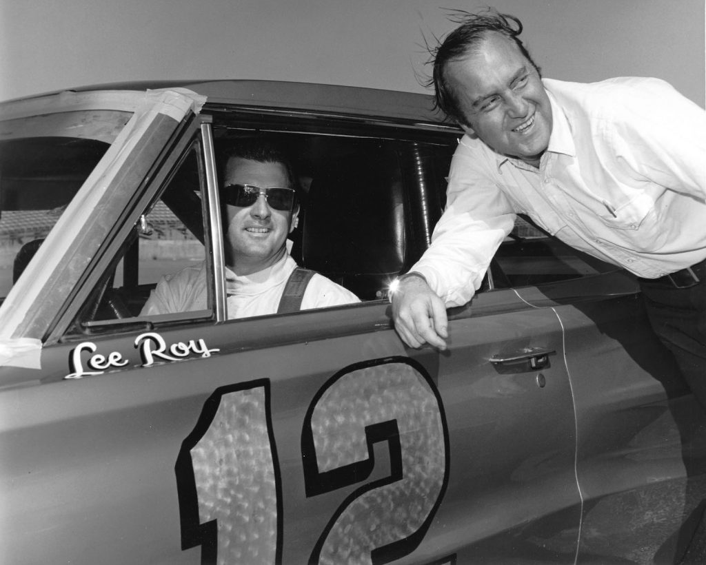 DAYTONA BEACH, FL — February 1966:  Motorsports journalist Brock Yates (R) with driver LeeRoy Yarbrough on pit road at Daytona International Speedway.  Yarbrough drove Jon Thorne's Dodge Charger to an eighth place finish in the Daytona 500 NASCAR Cup race.  (Photo by ISC Images & Archives via Getty Images) How Did the Cannonball Run Record Start?