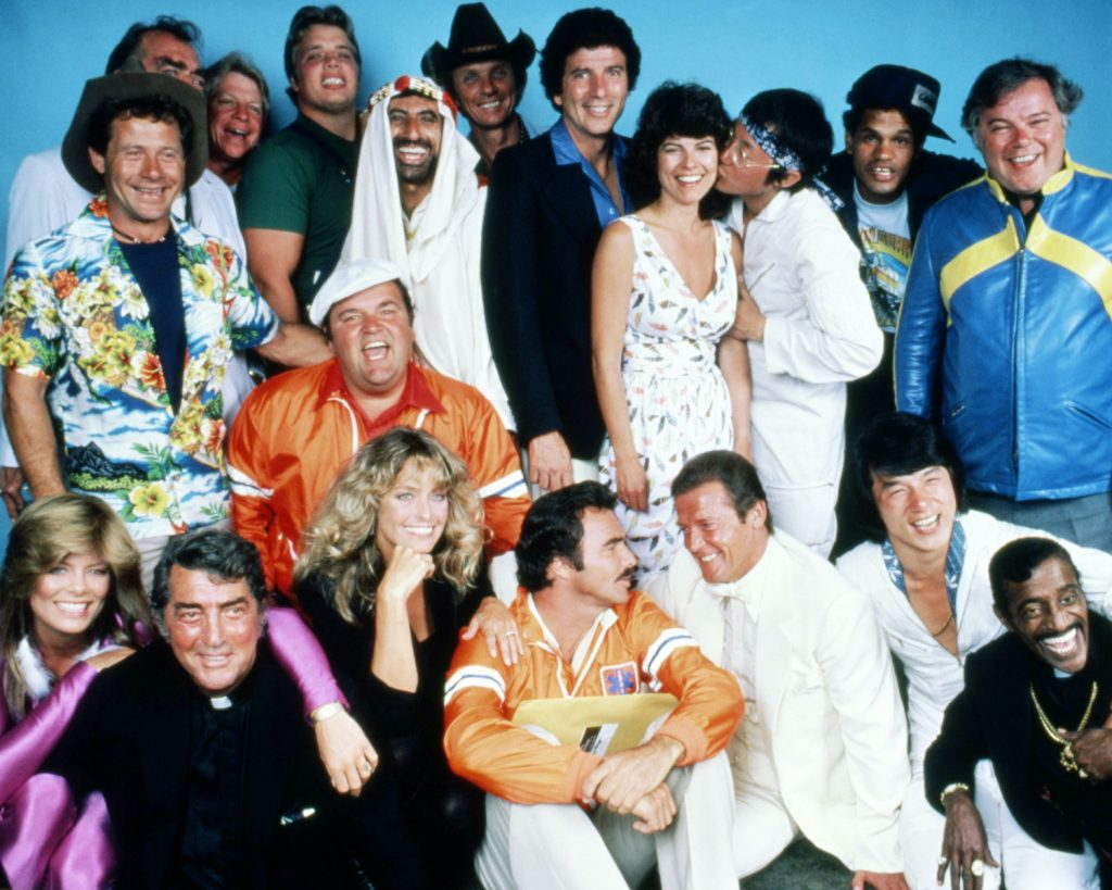 The cast of 'The Cannonball Run', directed by Hal Needham, 1981. Back row, left to right: Alfie Wise, Jack Elam (hidden), unknown, Joe Klecko, Jamie Farr, Mel Tillis, Bert Convy, Adrienne Barbeau, Michael Hui, Rick Aviles, and Warren Berlinger. Centre (in orange) Dom DeLuise. Front row, left to right: Tara Buckman, Dean Martin, Farrah Fawcett, Burt Reynolds, Roger Moore, Jackie Chan and Sammy Davis, Jr. (Photo by Silver Screen Collection/Getty Images) How Did the Cannonball Run Record Start?