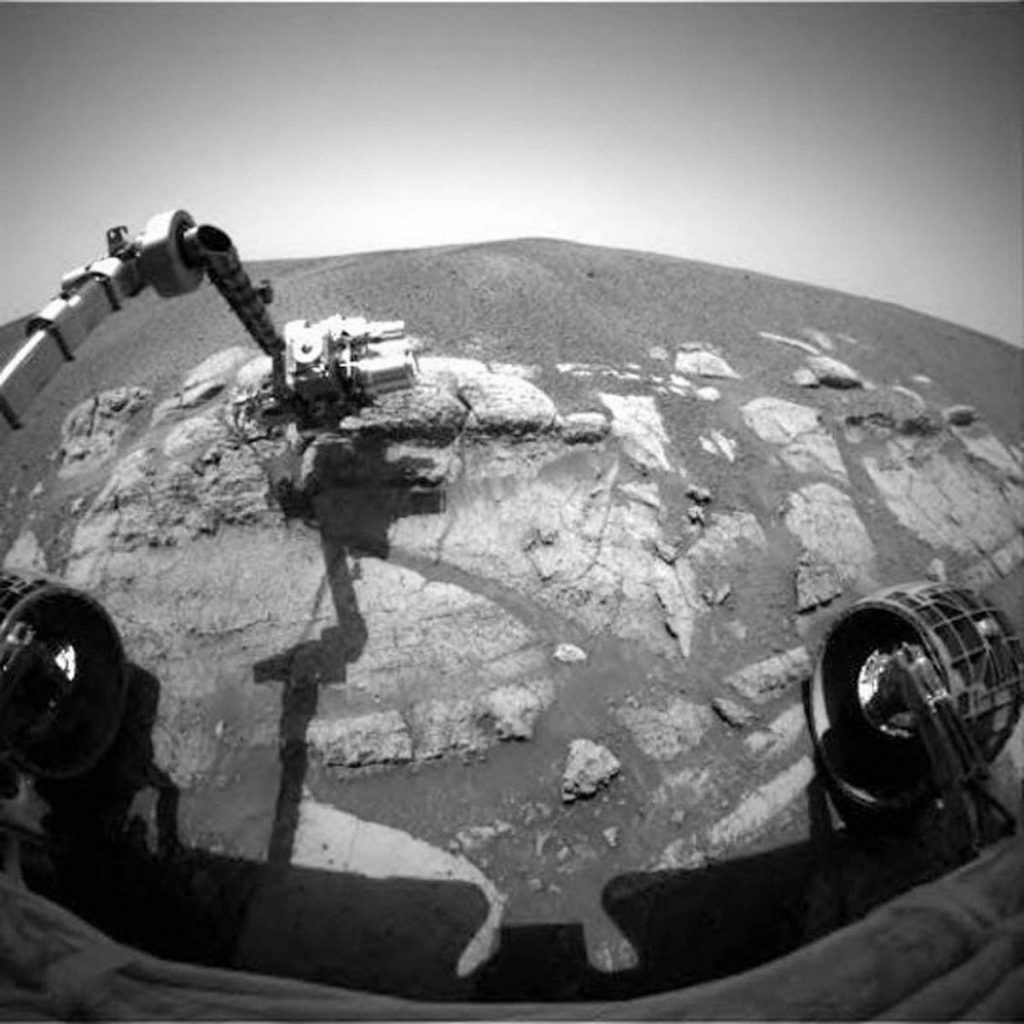black and white image taken from a Mars rover of the rover arm grabbing some samples