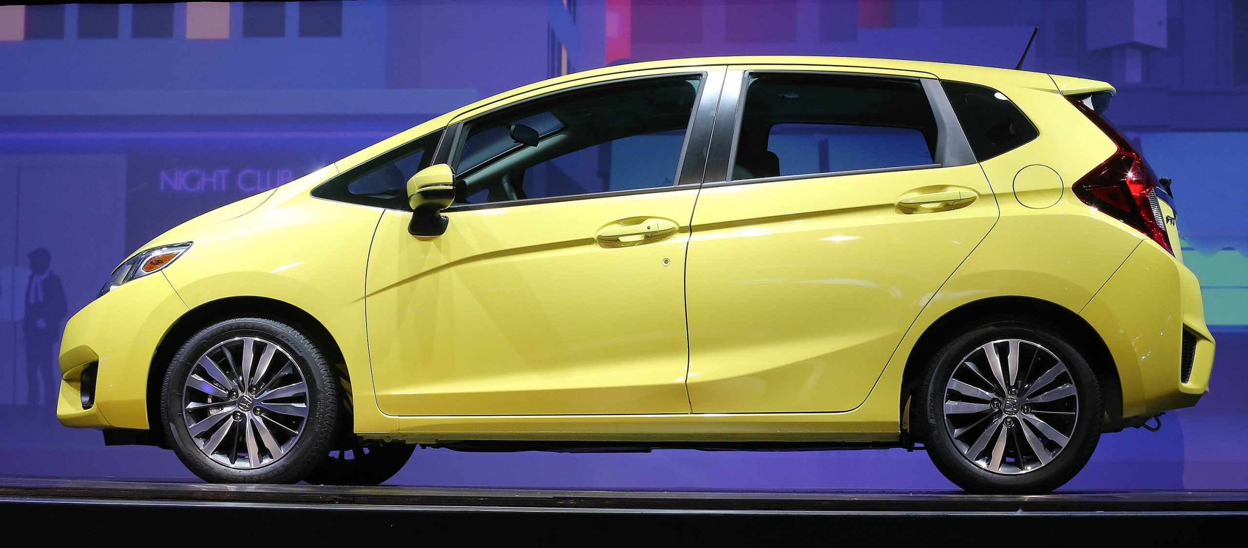 A yellow 2015 Honda Fit subcompact car shot in profile at an auto show