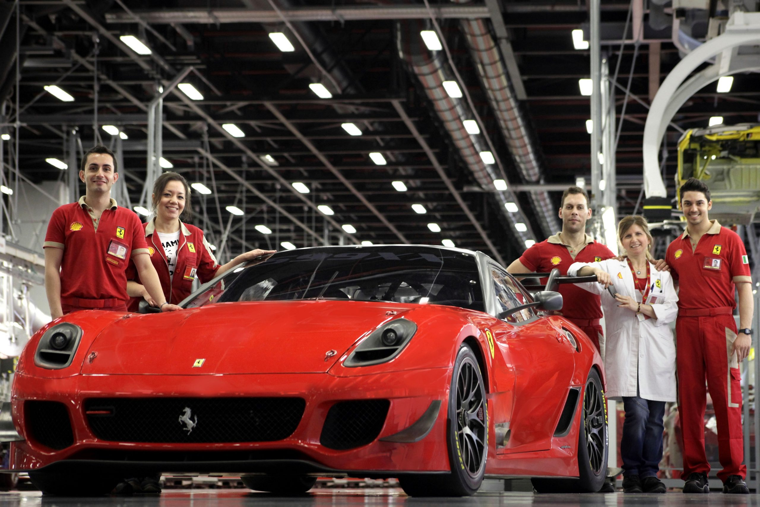 A handful of Ferrari factory workers, dressed in red, stand next to a complete Ferrari 599xx Evolution in Maranello