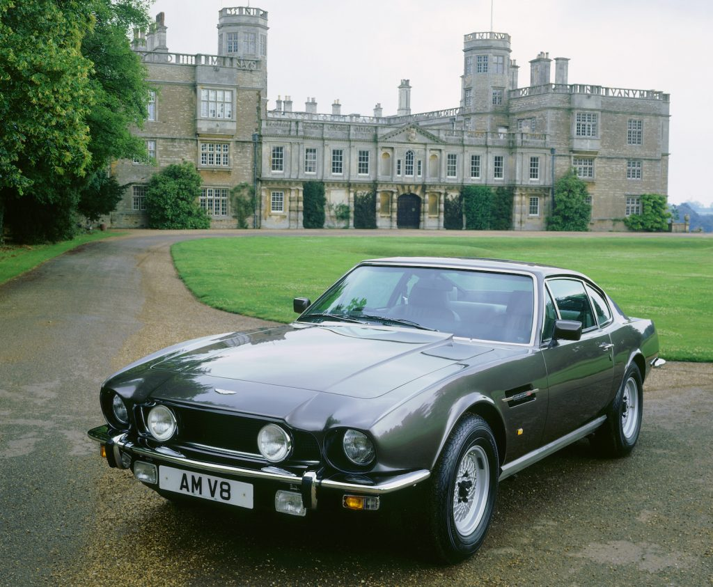 This is a gray 1987 Aston Martin V8 Coupe in front of a mansion. An identical car was one of James Bond's Classic cars (Photo by National Motor Museum/Heritage Images/Getty Images)