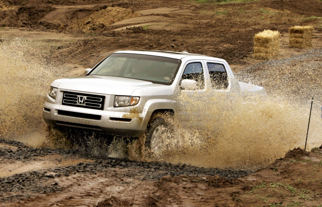 A silver Honda Ridgeline pickup truck is off-roading in the mud.