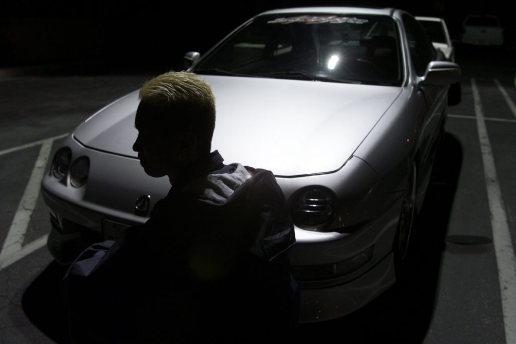 A man sits in the shadows in front of a first-generation Acura Integra