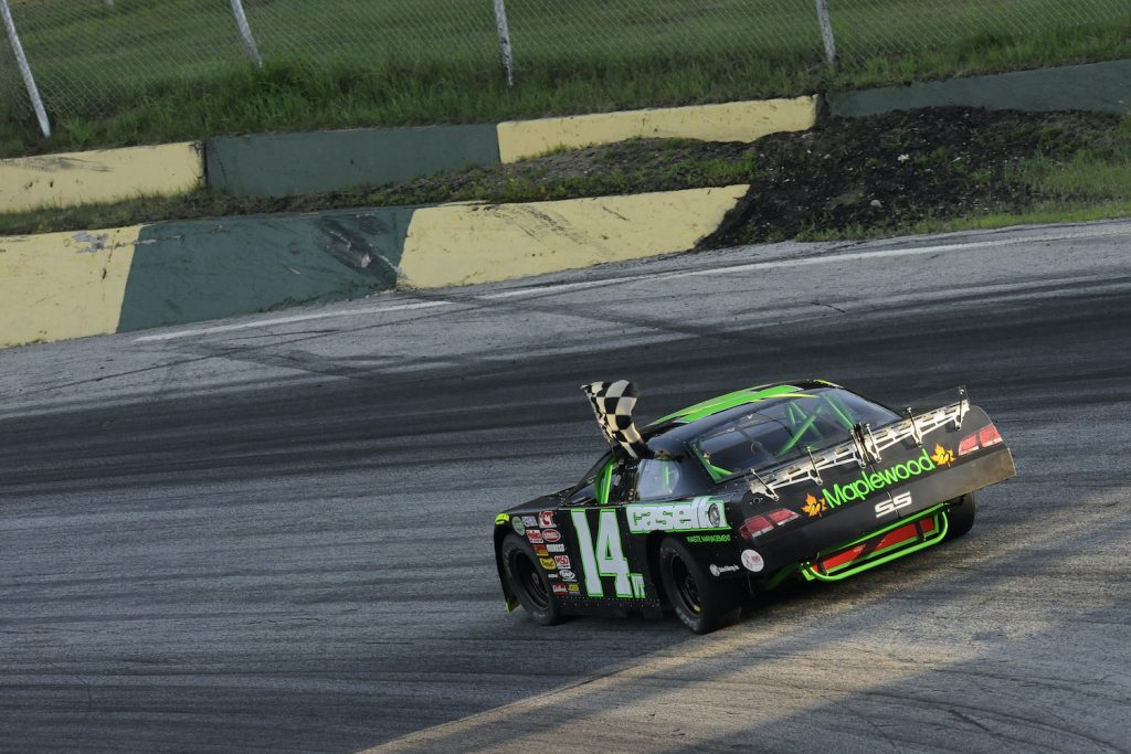 2014 July 24   Thursday: Phil Scott (14VT) Chevrolet Impala SS with the checkered flag after winning the third heat race for the Safelite 50 American Canadian Tour (ACT) late model feature at Thunder Road Speedbowl in Barre, Vermont. Scott is the Lt. Governor of Vermont. (Photo by David Allio/Icon SMI/Corbis/Icon Sportswire via Getty Images) Governor Phil Scott is a race car driver and set a COVID vaccination record.