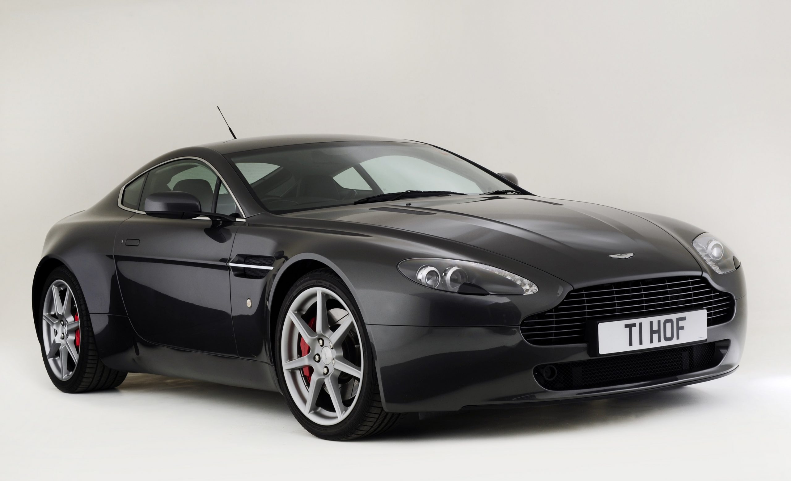 A black Aston Martin Vantage coupe shot from the front 3/4 angle in a studio booth