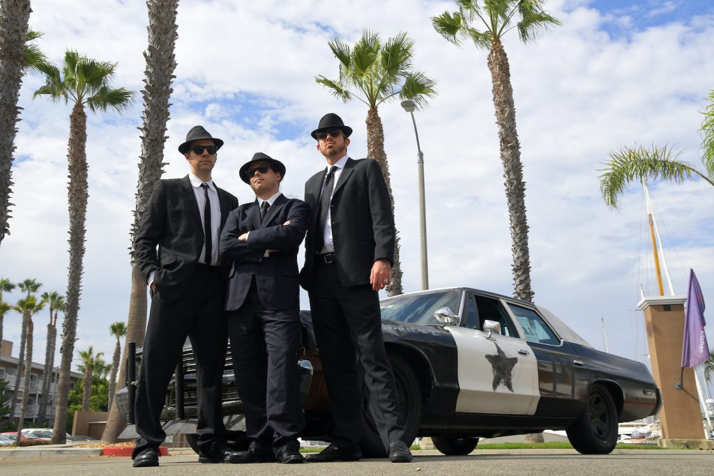 REDONDO BEACH, CA - SEPTEMBER 19: Arne Toman, 41, of Chicago, left, Forrest Sibley, 31, Atlanta , center, and Ed Bolian, 30, of Atlanta drove the 1974 Dodge Monaco Bluemobile a 2003 Silverado V8 to a first place finish in 34 hours 16 minutes where they pose September 19, 2016 in Redondo Beach, CA. (Photo by Katherine Frey/The Washington Post via Getty Images) Two holders of The Cannonball Run Record