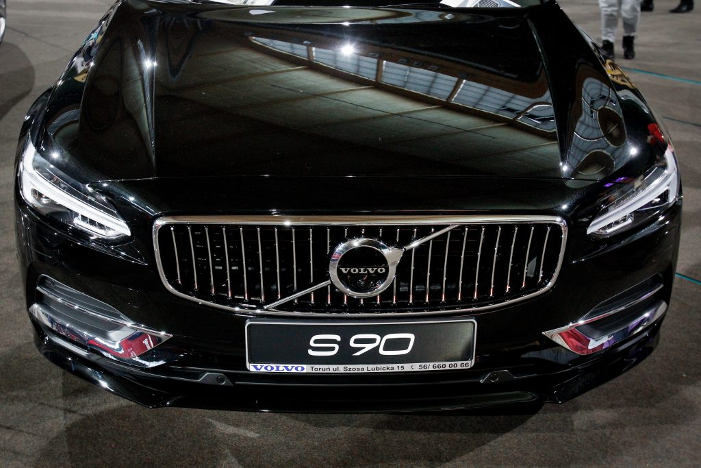 A black Volvo S90 shot from the hood down at an auto show
