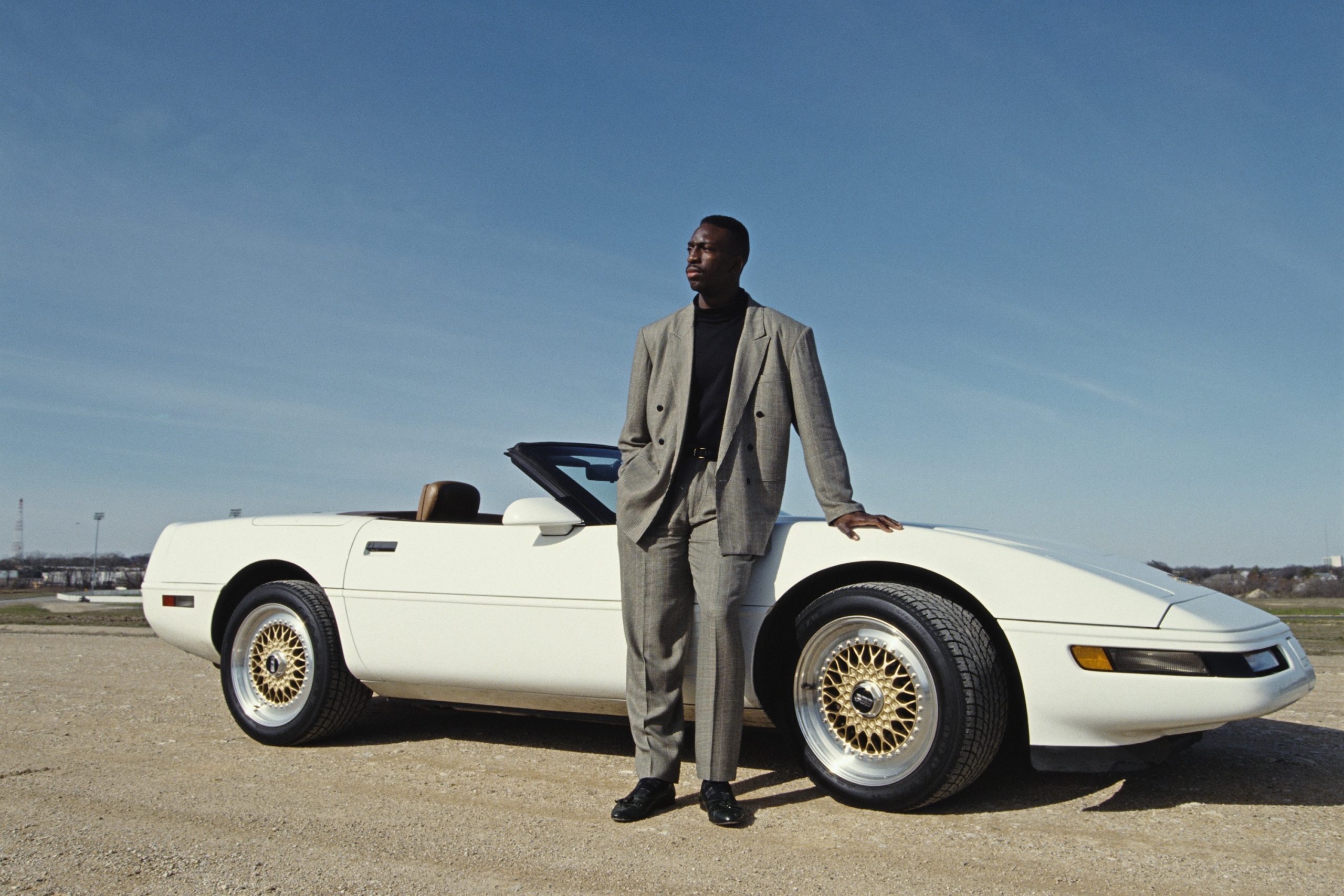 Olympic runner Michael Johnson stands in front of his white C4 convertible with BBS gold wheels