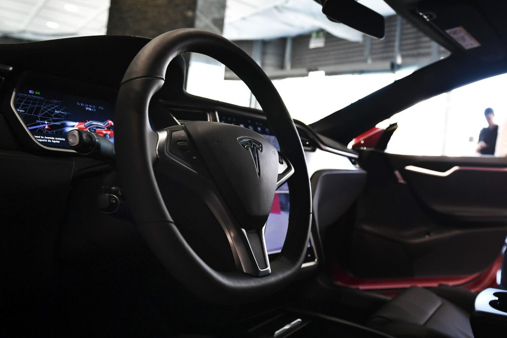 The interior of a standard Tesla Model S, complete with a regular old circular wheel.