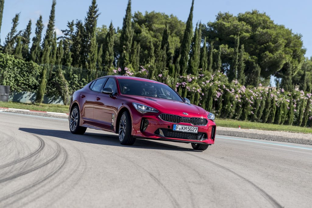 The Kia Stinger luxury car on a race track, shot from the low front 3/4 angle