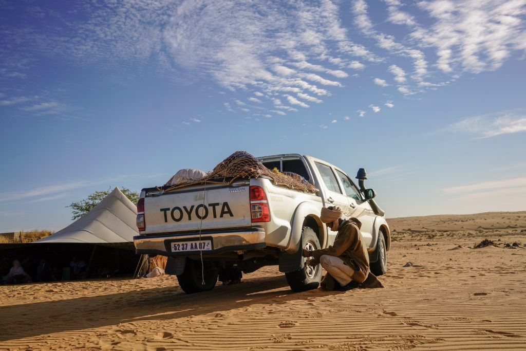 A driver for hire adjusts a Toyota truck's tire pressure for Saharan sand dunes in Oudane Mauritania. Instead of an electric Toyota Tundra, the world's largest automaker developed a next generation internal combustion drivetrain.   David Degner/Getty Images