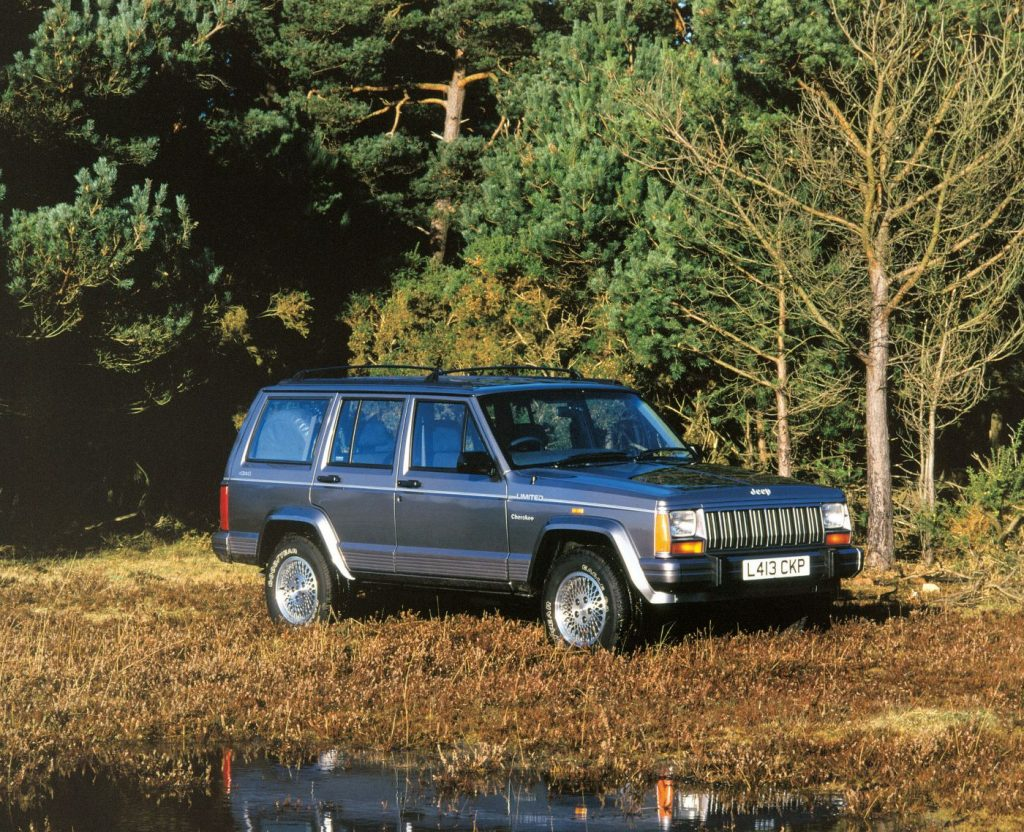 Gray 1993 Jeep Cherokee parked next to a forest