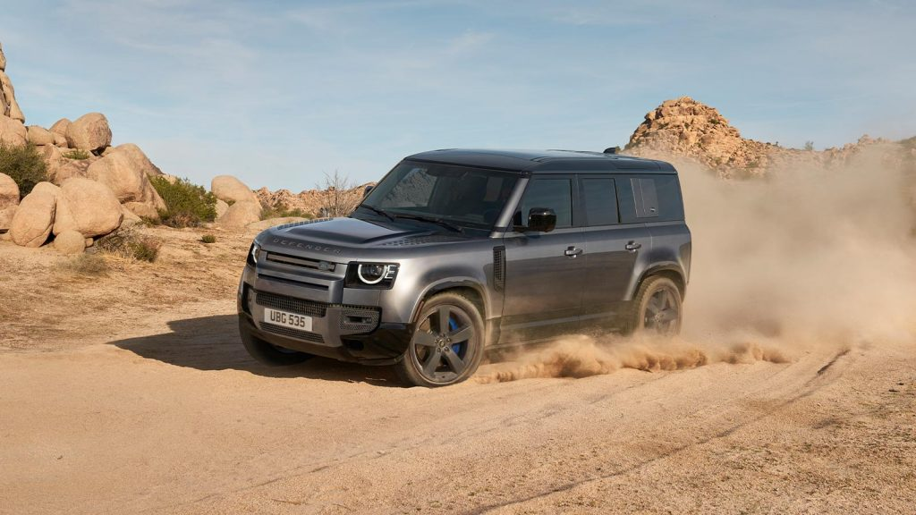 Gray 2021 Land Rover Defender driving by large boulders