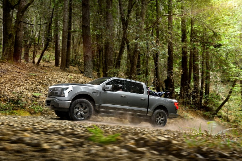 Gray 2022 Ford F-150 Lightning driving through a forest