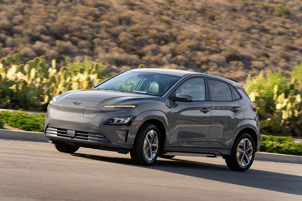 Gray 2022 Hyundai Kona Electric driving by some cacti