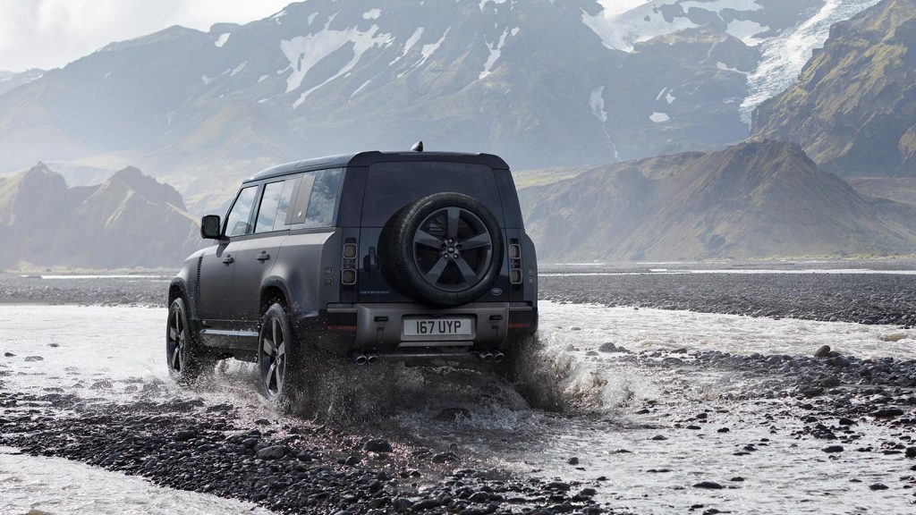 Gray 2022 Land Rover Defender driving through a stream