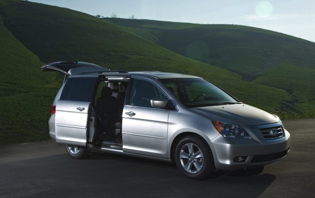 A honda odyssey is parked near a grassy hill at night with the doors open