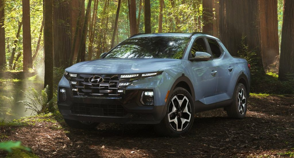 A blue Hyundai Santa Cruz small pickup truck is parked in the forest.