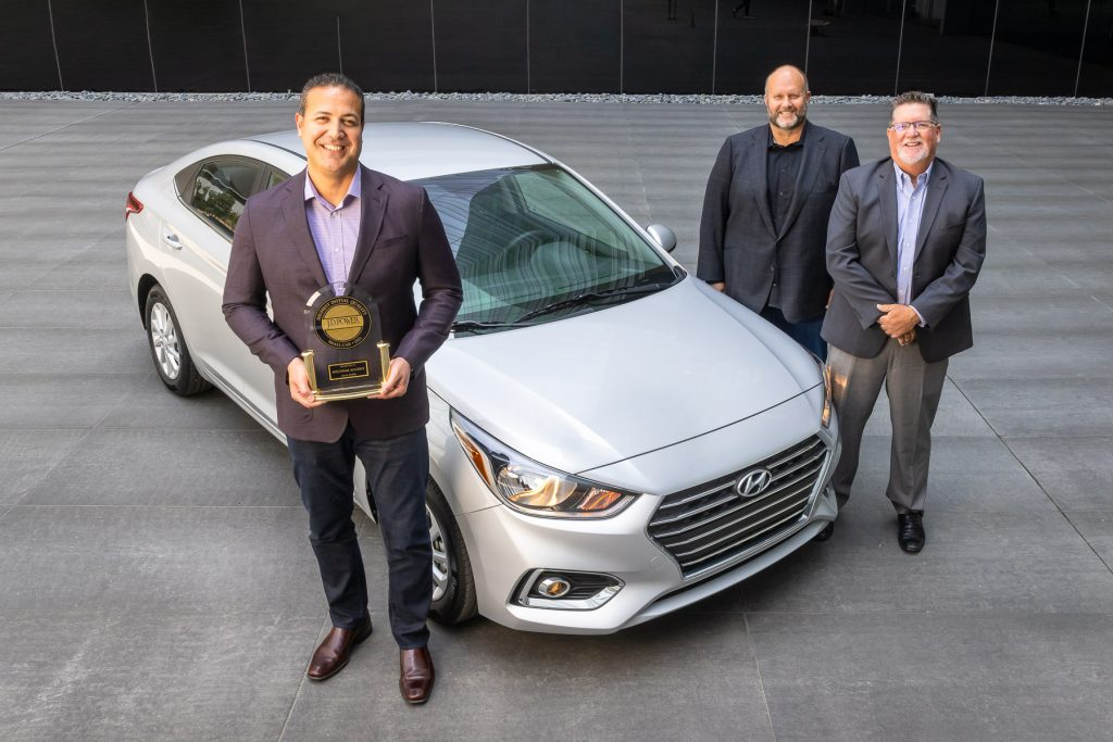 Hyundai executives standing next to a silver 2021 Hyundai Accent with the J.D. Power Initial Quality award