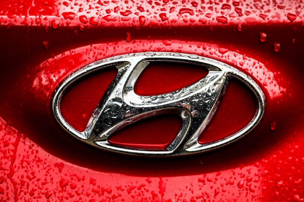 A chrome Hyundai logo on a red vehicle.