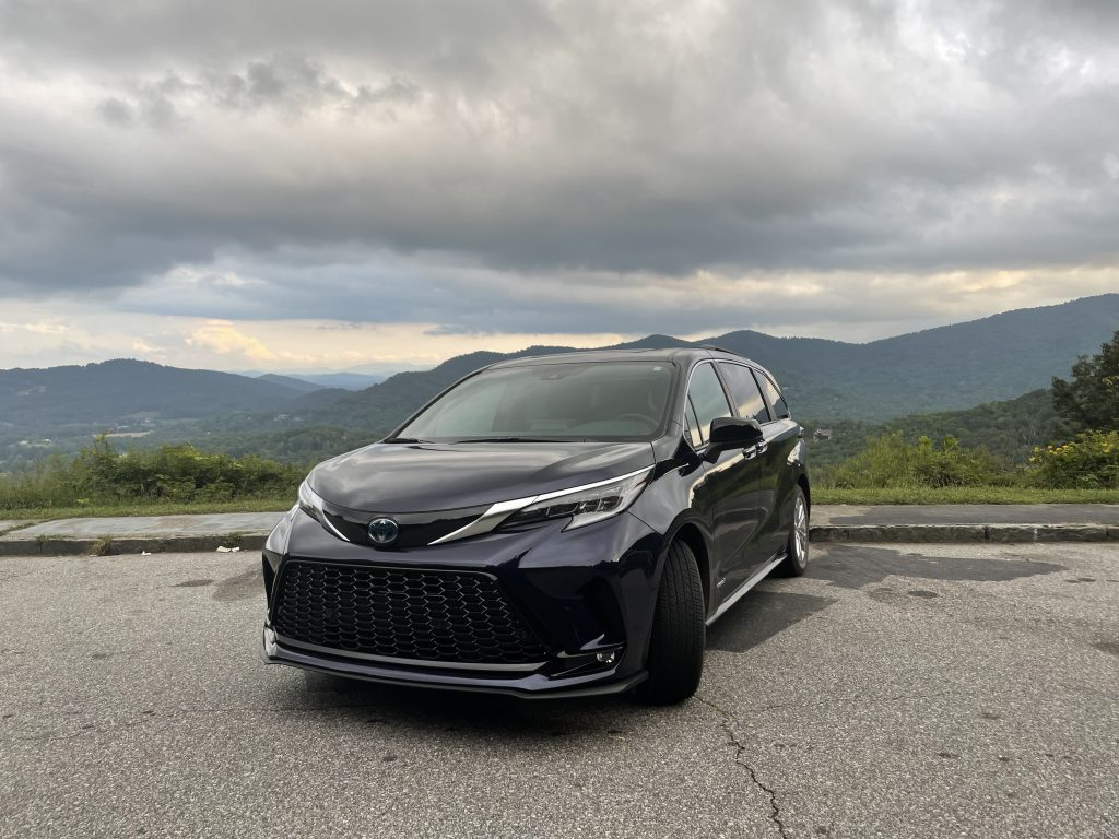 A gray 2021 Toyota Sienna in front of mountains.