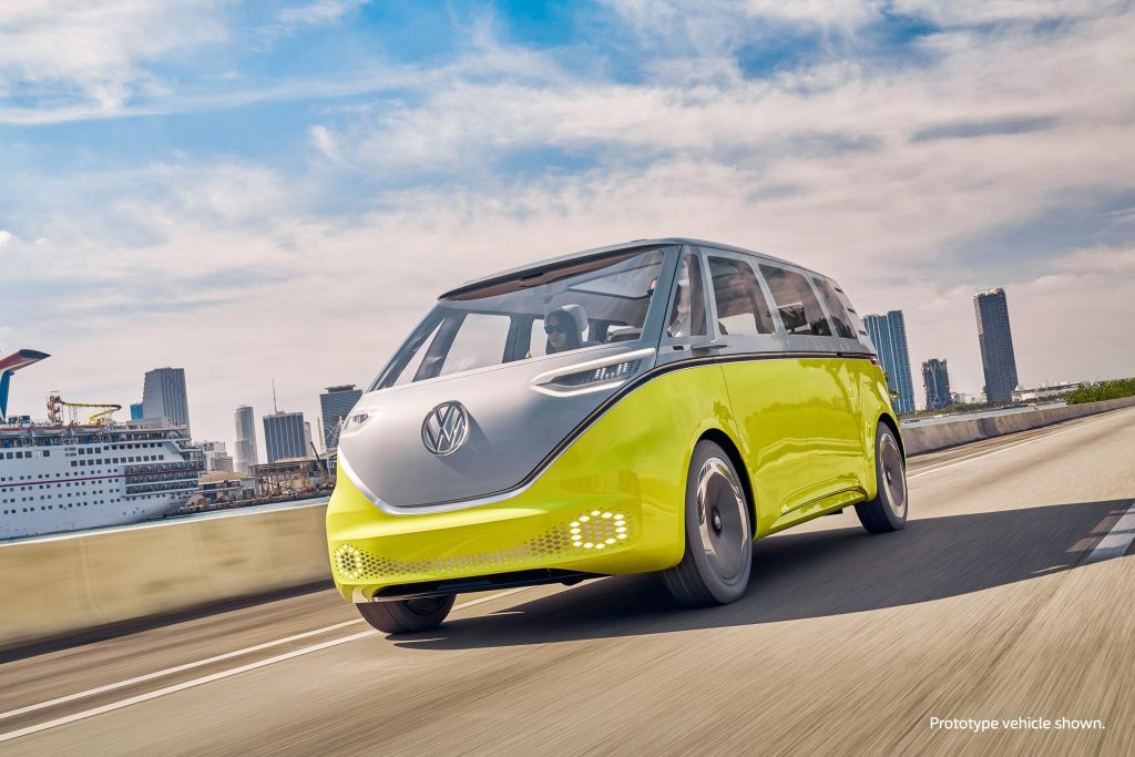A yellow Volkswagen ID.Buzz concept microbus drives down a road during the day