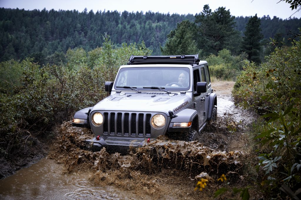 The 2021 Jeep Wrangler works its way through a muddy, forested trail