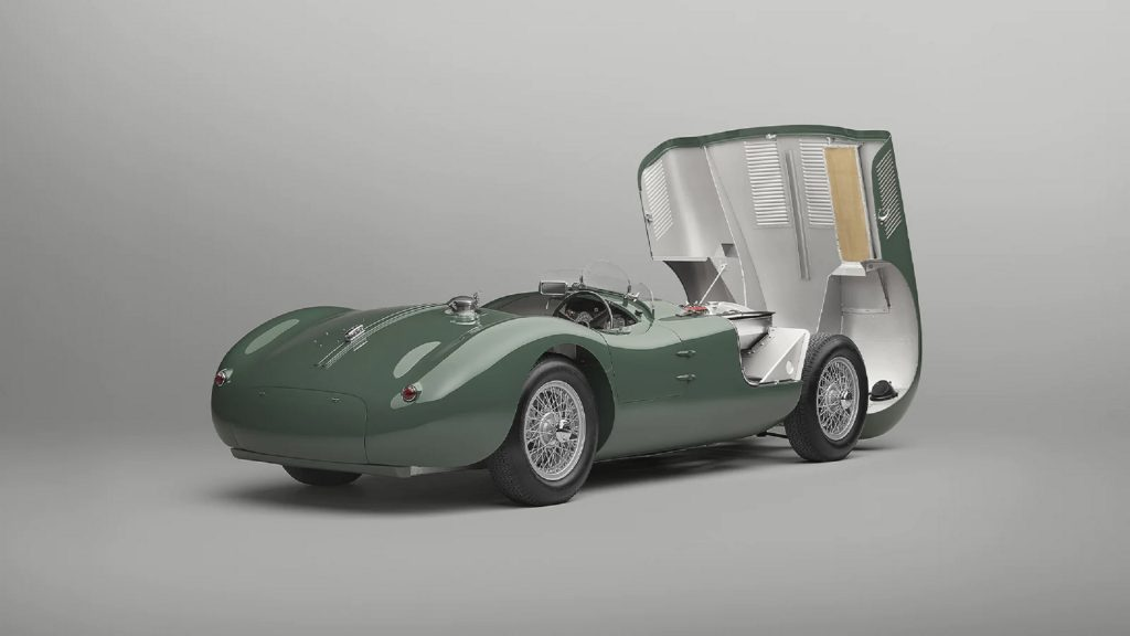 The rear 3/4 view of a green Jaguar C-Type Continuation with its hood open