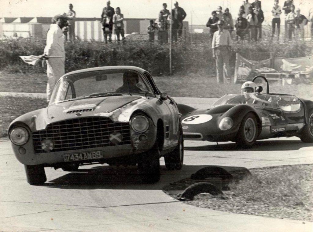 Vintage Jaguar XK140 barn find in a vintage photo racing a Ferrari