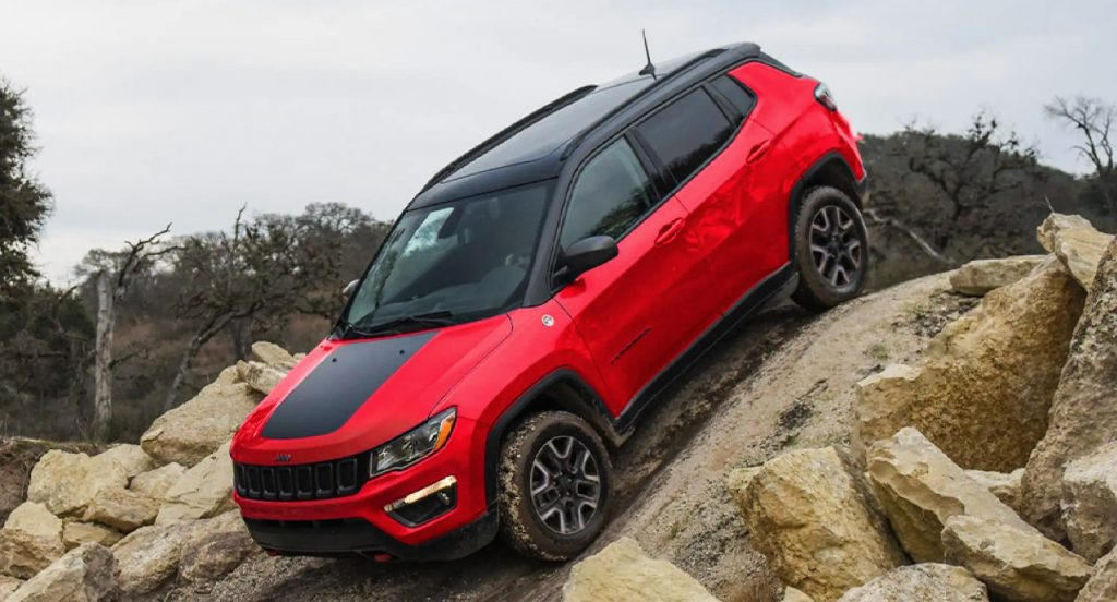 A red Jeep Compass Trailhawk package is descending down a hill surrounded by rocks.