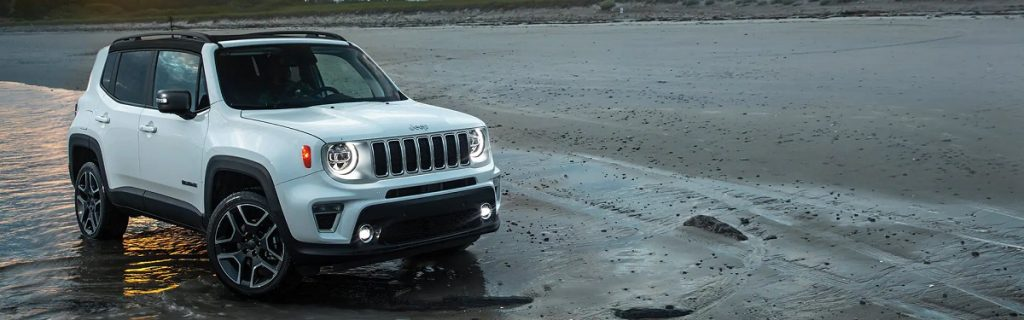 A white 2021 Jeep Renegade parked on the beach.