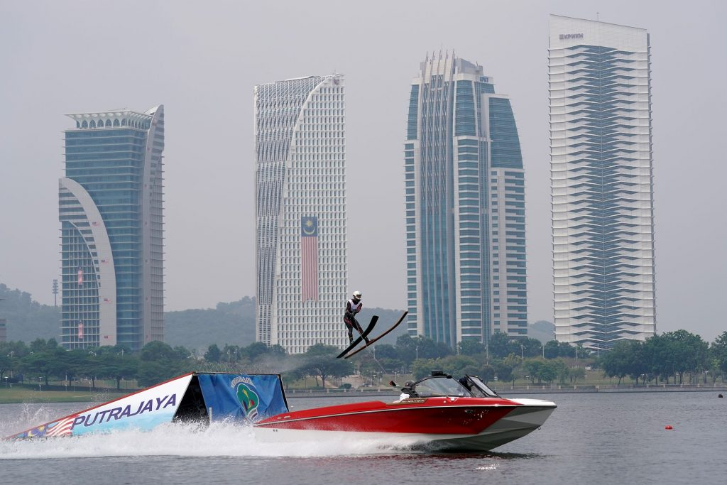 Jet boat on the water with a someone riding skis going up a ramp in front of a city skyline.